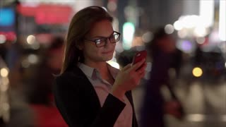 young women walking and texting on smart phone in the city at night