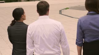 Businesspeople walking on plaza, slow motion shot at 240fps, steadycam shot