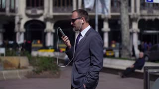 businessman with the headphones walking along the street and talking on his cellphone