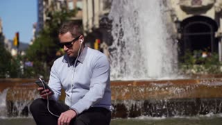 businessman sitting by the fountain and listening to music on his ipod