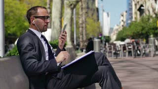 businessman sitting on a bench in the city