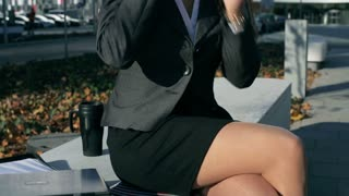 Businesswoman chatting on cellphone and smiling to the camera, steadycam shot