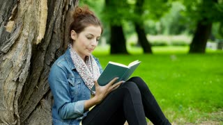 Absorbed girl leaning on tree in the park and reading a book