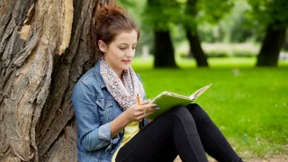 Absorbed girl leaning on tree in the park and writing something