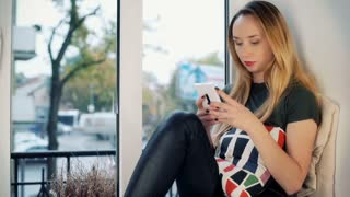 Absorbed girl sitting by the window and typing message on smartphone