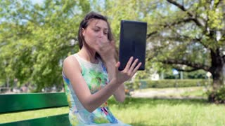 Absorbed girl sitting in the park and browsing something on tablet