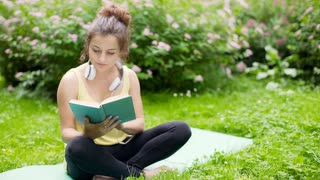 Absorbed girl sitting on exercising mat in the park and reading a book