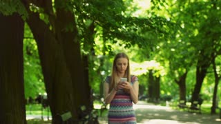 Absorbed girl walking in the park and texting on smartphone