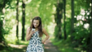 Absorbed girl walking on pathway in the forest and texting on smartphone