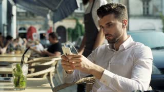 Absorbed man listening music and browsing internet on smartphone