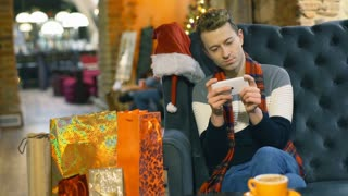 Absorbed man sitting in the festive cafe and texting on smartphone, steadycam sh