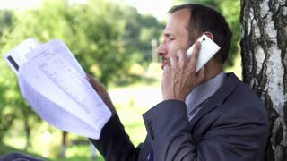 Angry businessman with documents screeming to the cellphone, 120fps