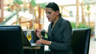Angry businesswoman beating broken laptop in the restaurant