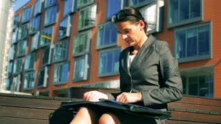 Angry businesswoman checking documents and tear paper into pieces