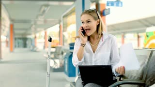 Angry businesswoman talking on cellphone while sitting on the train station