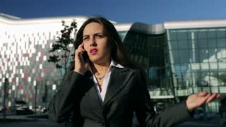 Angry businesswoman talking on cellphone while walking outside, steadycam shot