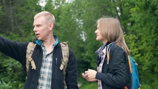 Angry couple arguing about direction while standing in the forest