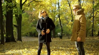 Angry couple having an argument in the autumnal park