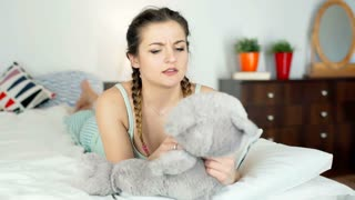 Angry girl lying on bed and and takes her emotions on teddy bear, steadycam shot