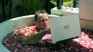 Angry man beating laptop and throwing it to the water