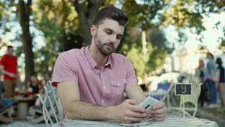 Angry man looking around and checking time on smartphone outdoors