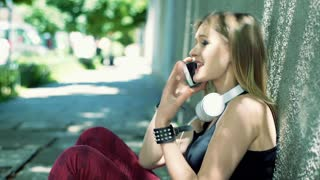 Angry, punk girl sitting on the pathway and talking on cellphone
