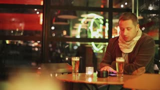 Anxious man waiting in pub and drinking beer, steadycam shot