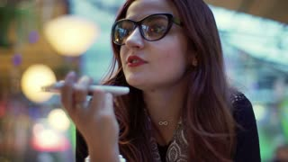 Attractive girl in glasses talking on loudspeaker