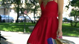 Attractive girl in red dress going round with shopping bags, slow motion shot at