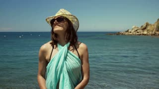Attractive woman in swimsuit walking next to the sea and enjoying it, steadycam