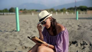 Attractive woman sitting on the beach and reading book