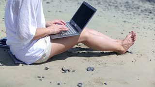 Attractive woman sitting on the beach and working on laptop