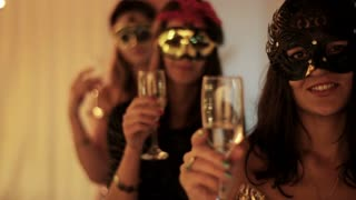 attractive women in masks holding glasses of champagne and smiling to the camera