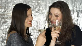 Attractive women making a toast to the camera and smiling, steadycam shot