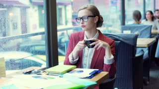 Beautiful businesswoman drinking coffee and looking thoughtful