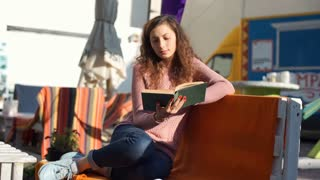 Beautiful girl reading book outdoors and smiling to the camera