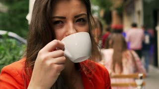 Beautiful woman drinking coffee and relaxing in the street cafe