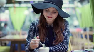 Beautiful woman eating mousse and smiling to the camera