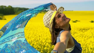 Beautiful woman holding scarf on rapeseed's field, steadycam shot, slow motion s