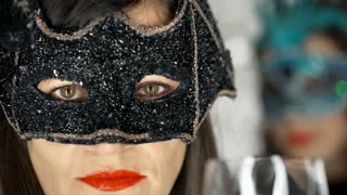 Beautiful woman in black, carnival mask looking to the camera, steadycam shot