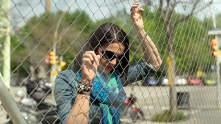 Beautiful woman leaning on wire fence and looking to the camera, steadycam shot