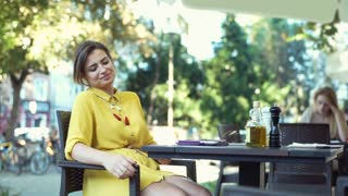 Beautiful woman sitting in the outdoor cafe and relaxing