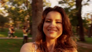 Beautiful woman spinning around in the park and smiling, steadycam shot