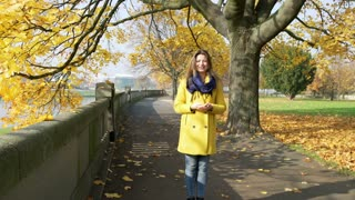 Beautiful woman standing in the autumnal park and talking to the camera