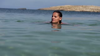 Beautiful woman swimming in the sea, slow motion shot at 120fps