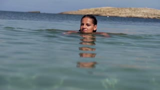 Beautiful woman swimming in the sea, slow motion shot at 240fps