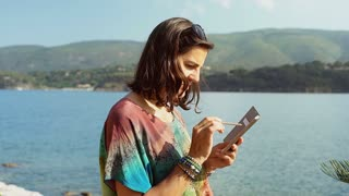 Beautiful woman using stylus while browsing internet on smartphone next to the s