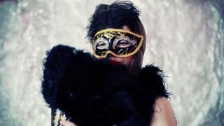 Beautiful woman wearing carnival mask and holding fan