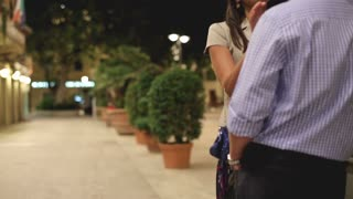 Beautiful young couple flirting in city night