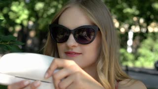 Blonde girl sitting in the park and looking on her new glasses